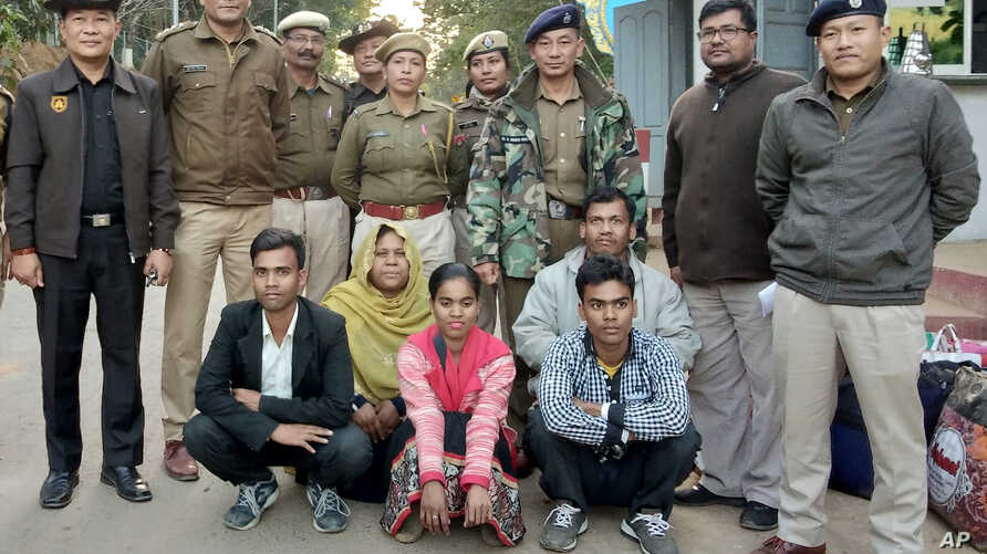Members of a Muslim Rohingya family sit as they pose for a photograph with Indian and Myanmar security officials before their deportation on India-Myanmar border at Moreh in the northeastern state of Manipur, India, Jan. 3, 2019.