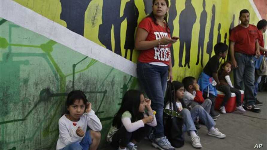 Sandra Ramirez stands with four of her children along the walkway to the United States to support members of the group Border Dreamers, Tijuana, Mexico, March 10, 2014.
