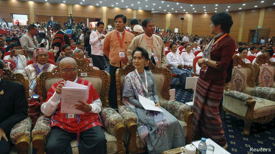 Myanmar's Aung San Suu Kyi smiles as she arrives to give a speech during talks between the government, army and representatives of ethnic armed groups over a ceasefire to end insurgencies, in Naypyitaw, Jan. 12, 2016.