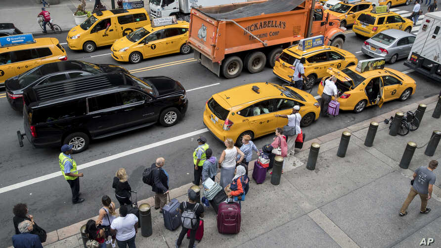 FILE - Passengers board yellow cabs as others wait in line at a taxi stand on 42nd Street outside Grand Central Terminal in New York, Aug. 1, 2018.