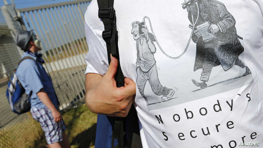 """A protester outside the """"Dagger Complex"""", which is used by the U.S. Army intelligence services, during a demonstration against the NSA and in support of Edward Snowden in Griesheim, Germany, July 20, 2013."""