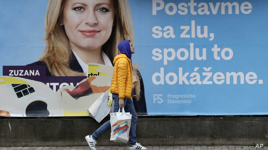 A man walks past a campaign poster for Zuzana Caputova in Bratislava, Slovakia, Friday, March 15, 2019. Caputova is one of the favorite candidates to succeed Slovakia's President Andrej Kiska in the upcoming election.