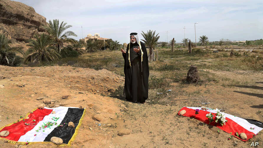 FILE - An Iraqi man prays for his slain relative at the site of a mass grave believed to contain the bodies of Iraqi soldiers killed by Islamic State group militants when they overran Camp Speicher military base, in Tikrit, Iraq.
