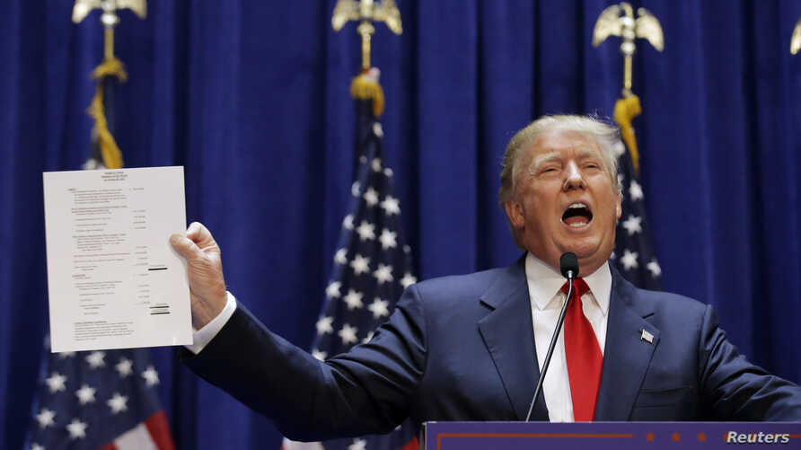 U.S. Republican presidential candidate, real estate mogul and TV personality Donald Trump holds up his financial statement showing his net worth as he formally announces his campaign for the 2016 Republican presidential nomination during an event at