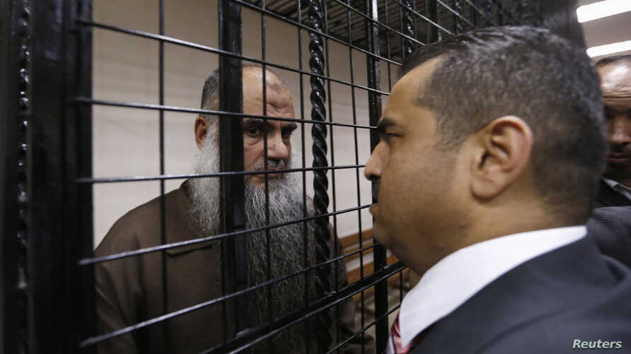 Radical Muslim cleric Abu Qatada, left, speaks with his lawyer Hussein Mubadeen after his trial at the State Security Court in Amman, Jordan, June 26, 2014.