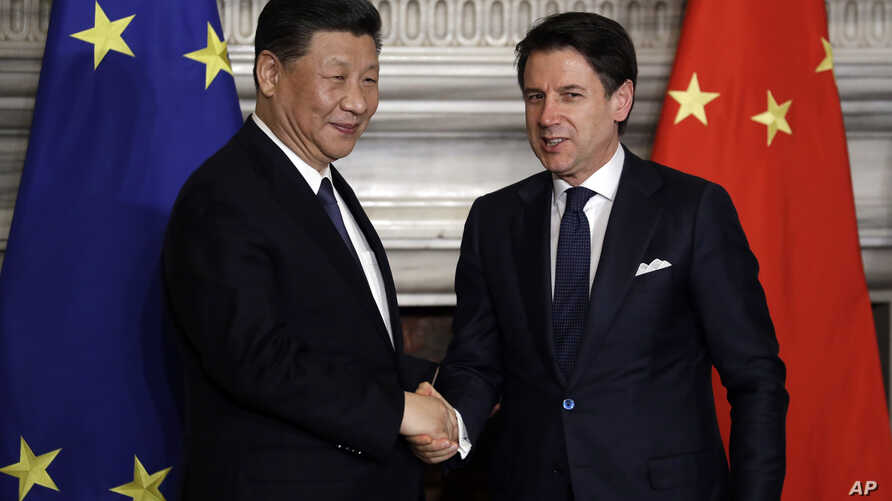 """Chinese President Xi Jinping, left, and Italian Prime Minister Giuseppe Conte shake their hands following the signing of a memorandum in support of Beijing's """"Belt and Road"""" initiative, at Rome's Villa Madama, March 23, 2019."""