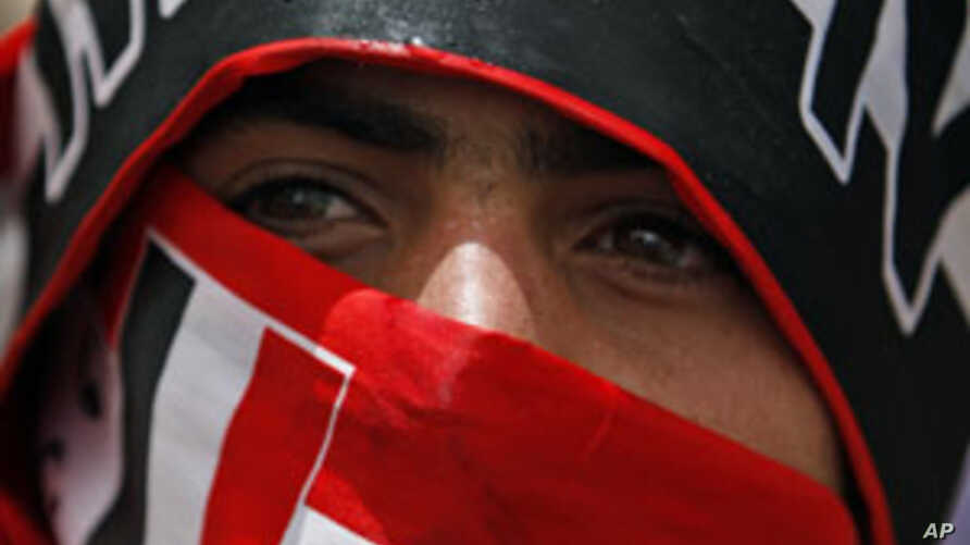 An anti-government protester wraps a Yemeni flag around his mouth during a demonstration to demand the ouster of Yemen's President Ali Abdullah Saleh in Sanaa, May 23, 2011