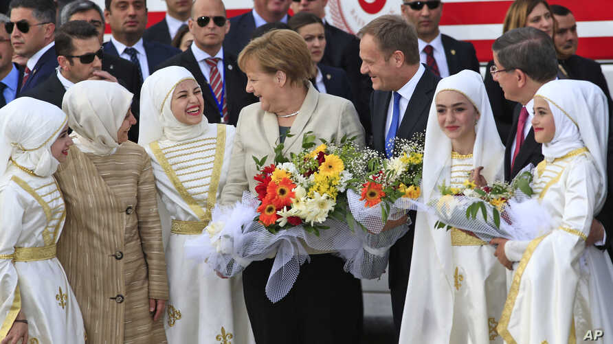 German Chancellor Angela Merkel, centre, accompanied by EU Council President Donald Tusk, right, talks to young women during a visit to the Nizip refugee camp in Gaziantep province, southeastern Turkey,  April 23, 2016.