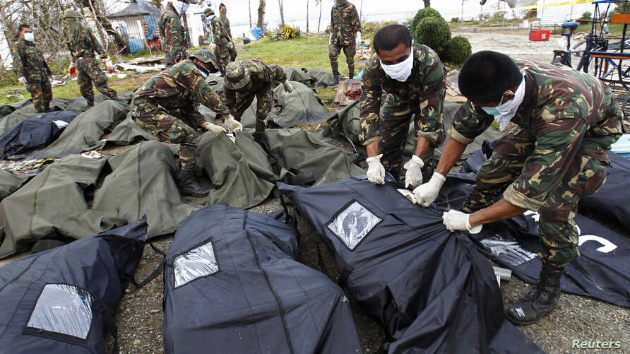 Soldiers zip up body bags after families have identified their relatives who perished during super typhoon Haiyan in Tacloban city, central Philippines, Nov. 13, 2013.
