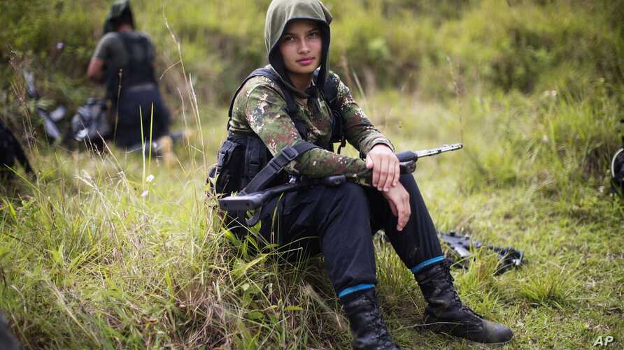 Juliana, a 20-year-old rebel fighter for the 36th Front of the Revolutionary Armed Forces of Colombia, or FARC, rests from a trek in the northwest Andes of Colombia, Jan. 6, 2016.