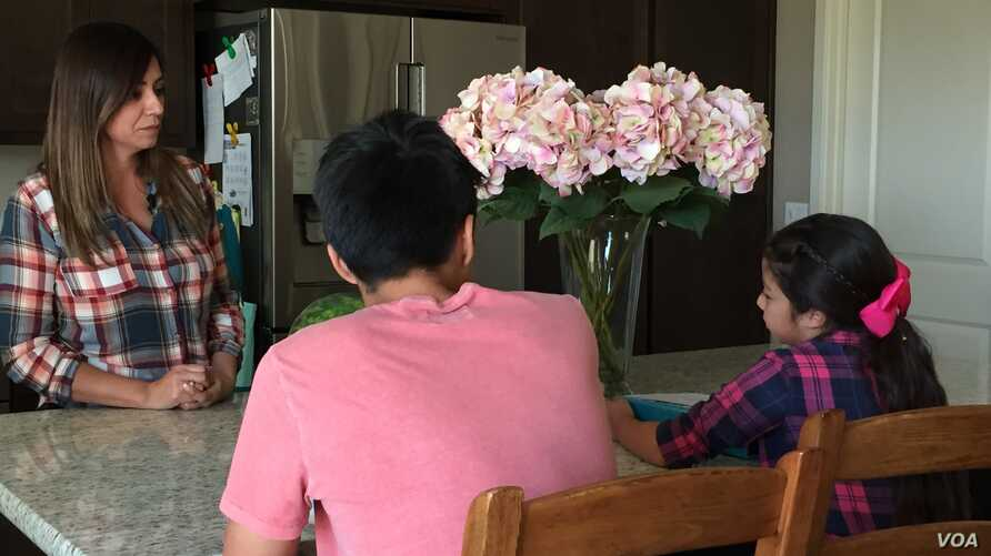 Felicia Luna, more relaxed after viewing her aneurysm through virtual reality, talks to her children on the day before her brain surgery.