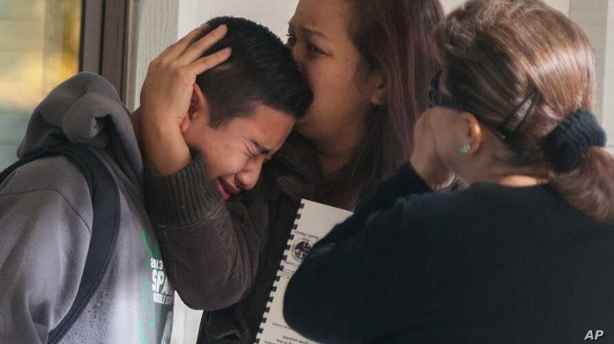 A Sparks Middle School student cries and is comforted after being released from Agnes Risley Elementary School, where some students were evacuated to after a shooting at SMS in Sparks, Nevada, Oct. 21, 2013.