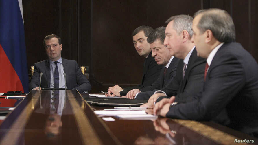 Russian Prime Minister Dmitry Medvedev (L) chairs a meeting with his deputies at the Gorki state residence outside Moscow, March 25, 2013.