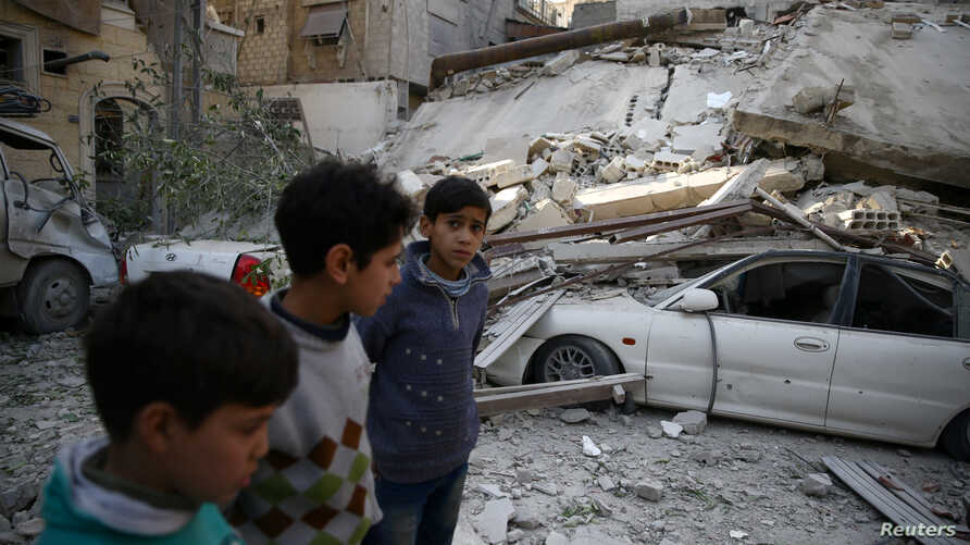 Children are seen near rubble after an airstrike in the besieged town of Douma, in eastern Ghouta, near Damascus, Syria, Feb 6, 2018.