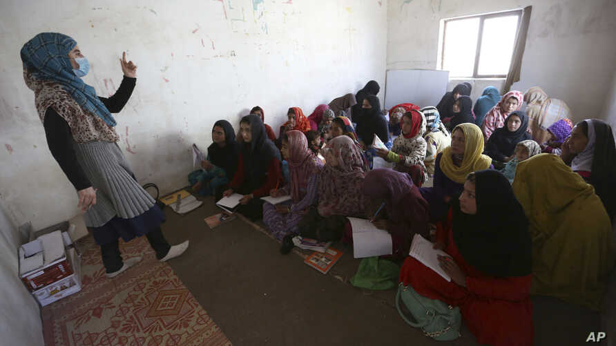 Afghan internally displaced school girls and women study at a class near their temporary homes on the outskirts of Kabul, Afghanistan, Oct. 30, 2017.