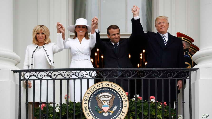President Donald Trump, French President Emmanuel Macron, first lady Melania Trump and Brigitte Macron hold hands on the White House balcony during a State Arrival Ceremony at the White House in Washington, April 24, 2018.