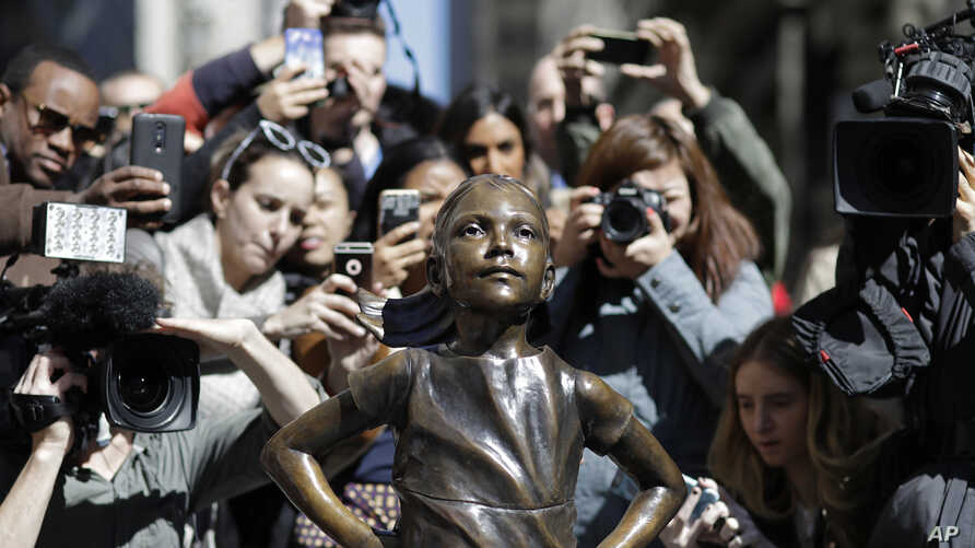 """People stop to photograph the """"Fearless Girl"""" statue, Wednesday, March 8, 2017, in New York."""