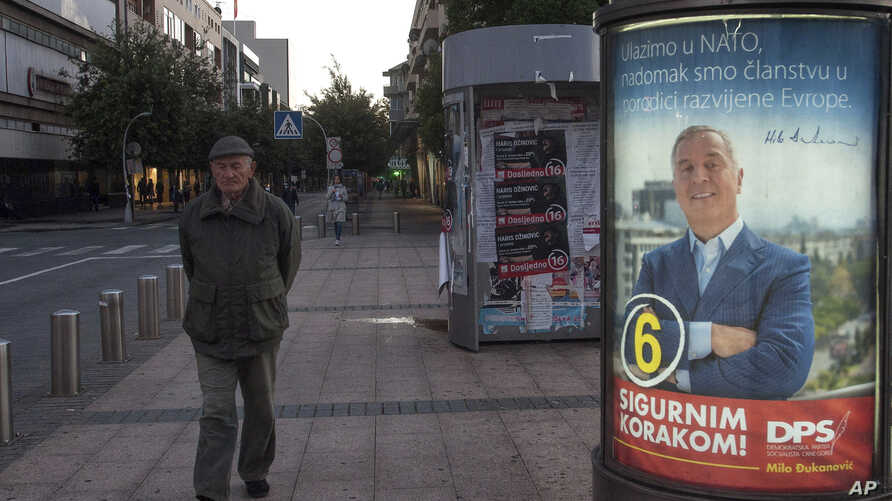 """A man walks by an election poster of pro-Western Prime Minister Milo Djukanovic, leader of the Democratic Party of Socialists, reading """"We are joining NATO, we are at the doorstep at the developed European family"""" and """"With firm step ahead!"""" in downt"""