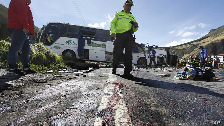 A police officer walks past a Colombian-registered bus that while traveling to Quito crashed in Pifo, Ecuador, Aug. 14, 2018.