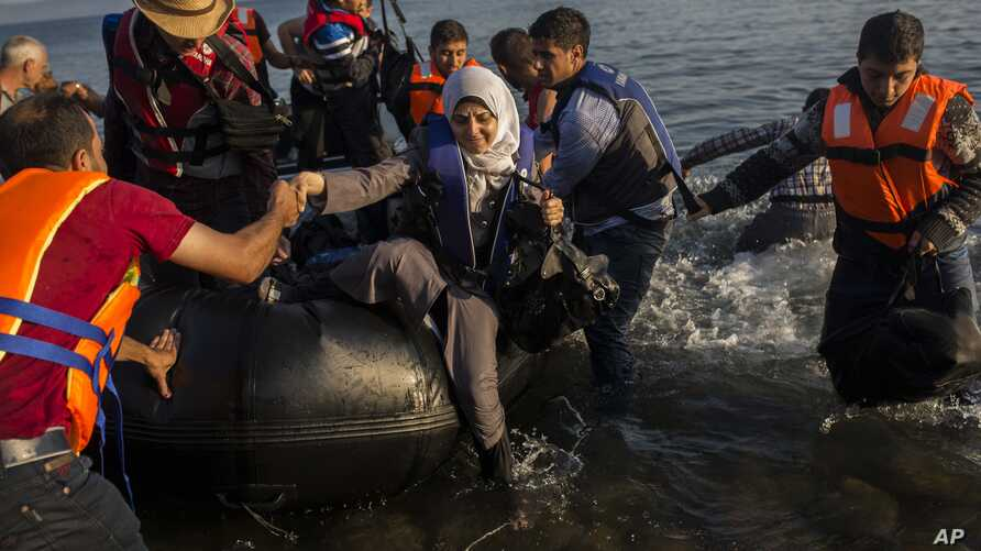 Migrants from Syria and Afghanistan arrive on an overcrowded dinghy from the Turkish coasts to the Greek island of Lesbos, Monday, July 27, 2015.