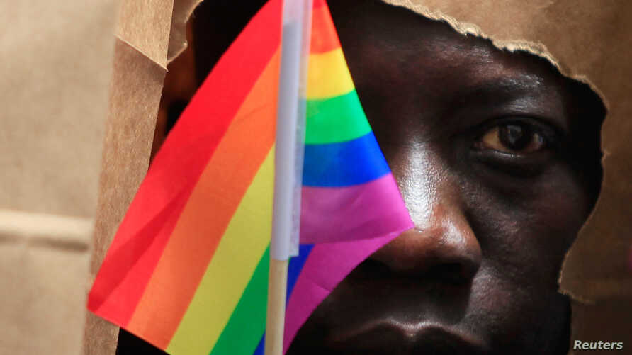 FILE - An asylum seeker from Uganda covers his face with a paper bag in order to protect his identity as he marches with the LGBT Asylum Support Task Force during the Gay Pride Parade in Boston, Massachusetts June 8, 2013.