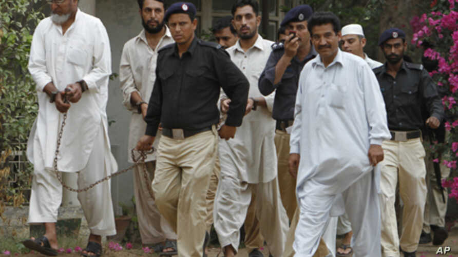 Pakistani police officers escort troops of a paramilitary force to an anti-terrorist court  to face charges in the June shooting death of an unarmed man in Karachi, Pakistan, Aug. 12, 2011.