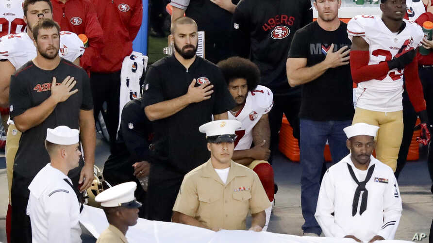 San Francisco 49ers quarterback Colin Kaepernick, middle, kneels during the national anthem before the team's NFL preseason football game against the San Diego Chargers, Thursday, Sept. 1, 2016.