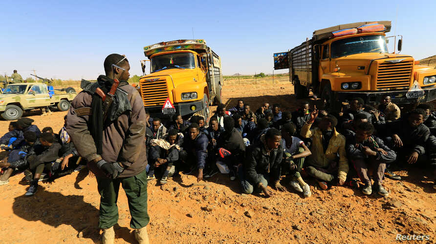 FILE - A member of Sudan's Rapid Support Forces (RSF) stands guard near illegal immigrants and traffickers, who according to the RSF were caught in a remote desert area en route to Libya, in Omdurman, Sudan January 8, 2017.