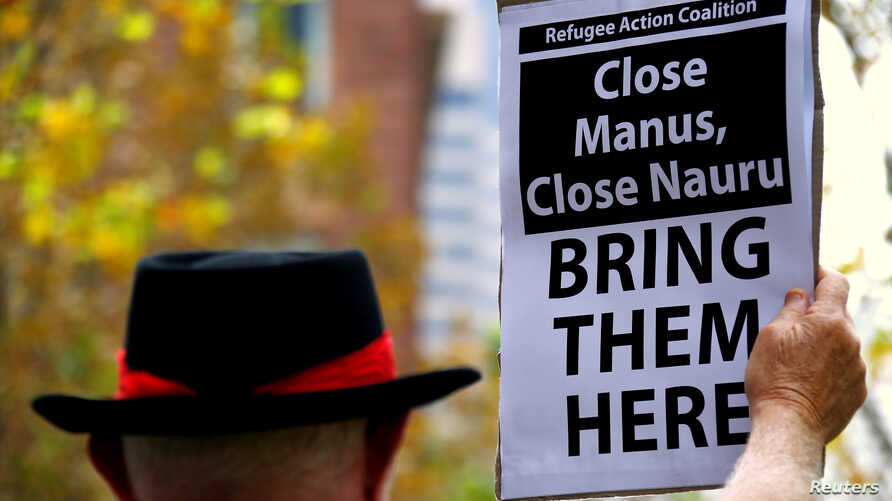FILE - A protester from the Refugee Action Coalition holds a placard during a demonstration outside the offices of the Australian Government Department of Immigration and Border Protection in Sydney, Australia, April 29, 2016.