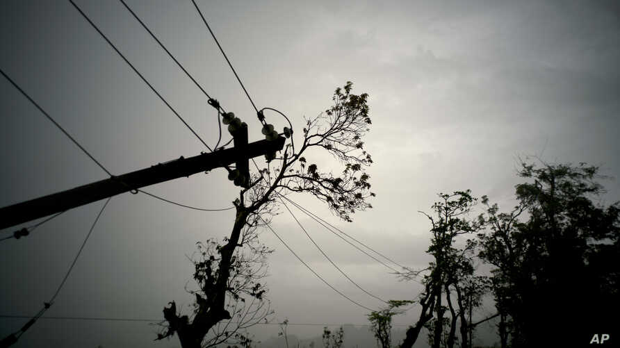 FILE - In this Oct. 16, 2017 file photo, power lines lay broken after the passage of Hurricane Maria in Dorado, Puerto Rico. Federal officials said on Jan. 8 2018, that efforts to fully restore power to Puerto Rico i should get a boost with more work