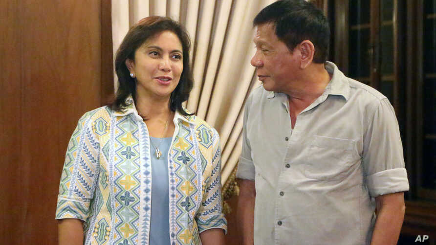 FILE - In this photo provided by the Office of the Vice-president (OVP), Philippines President Rodrigo Duterte meets with Vice President Leni Robredo during the latter's courtesy call at Malacanang Palace.