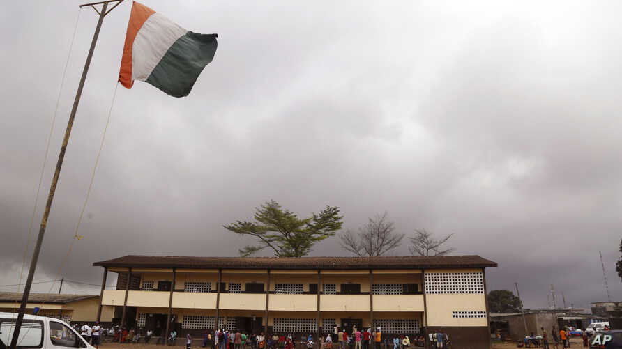 FILE - An Ivory Coast national flag, left, is seen at a polling station as people stand in line to vote in Abidjan, Ivory Coast, Oct. 25, 2015. Last year's orderly presidential election in the country was cited among the reasons for the lifting of sa