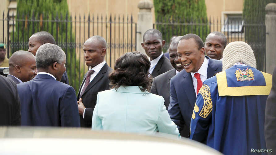 Kenyan President Uhuru Kenyatta (in red tie) is welcomed as he arrives at the Parliament Building to deliver his state of the nation address in Nairobi March 27, 2014.