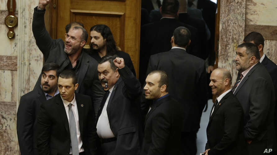 FILE - Lawmakers from the extreme right Golden Dawn party, shown outside parliament in Athens, and its leader will stand trial on criminal charges of participating in a criminal group, a judicial panel ruled Feb. 4, 2015.
