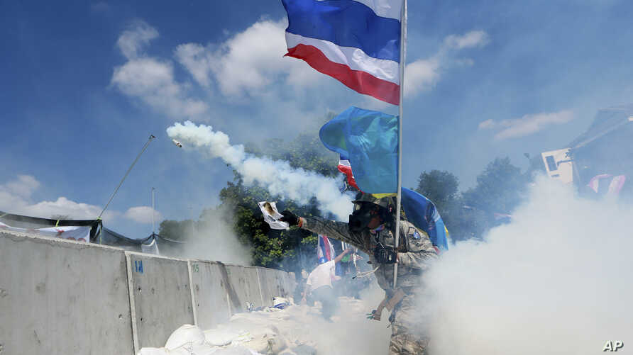 An anti-government protester throws back a tear gas canister fired by riot police in Bangkok, Thailand, Dec. 1, 2013.