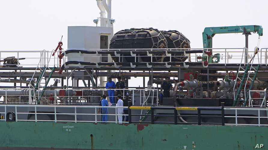Malaysian marine police officers inspect the Naniwa Maru 1 at Klang port, Malaysia after the Singapore-owned tanker was robbed by pirates, April 23, 2014.