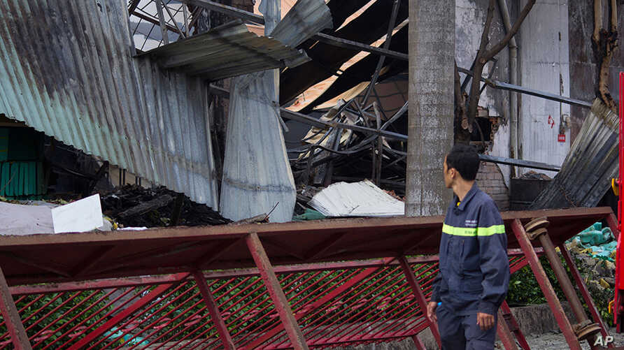 A man looks at the damaged building of Taiwanese bicycle factory Tan Than in Di An Town, Binh Duong Province, Vietnam, Wednesday, May 14, 2014.
