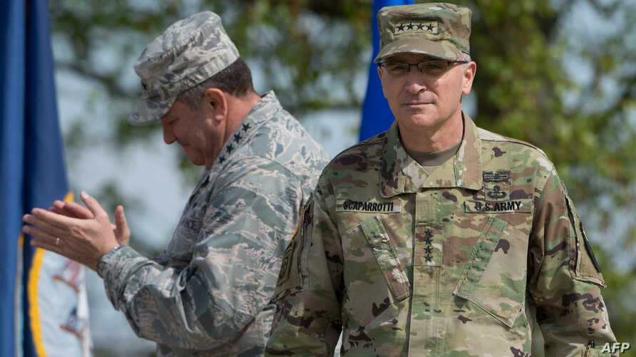 U.S. General Philip Breedlove (L) applauds as he stands next to U.S. General Curtis Scaparrotti during a ceremony on May 3, 2016, at the Patch Barracks in Stuttgart, southern Germany. During a ceremony, Breedlove handed over the U.S. European command
