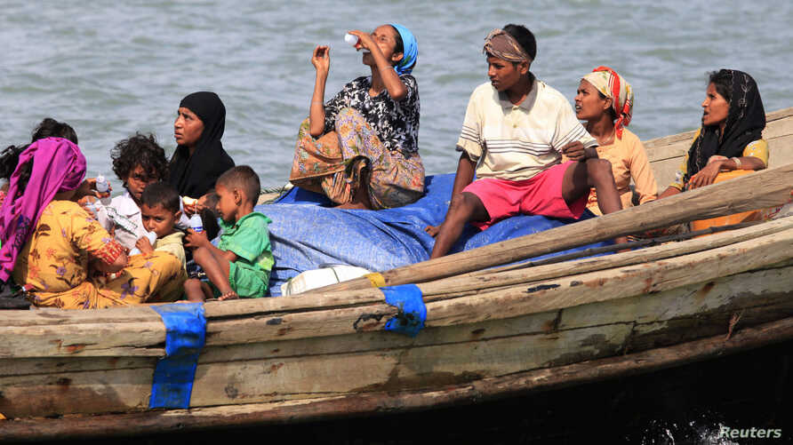 Muslim Rohingya people on a boat cross the river Naf, from Burma into Teknaf, Bangladesh, June 11, 2012.