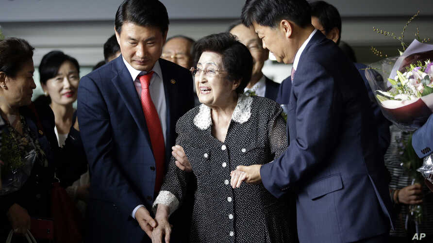 Lee Hee-ho, the widow of former South Korean President and Nobel Peace Prize laureate Kim Dae-jung, is escorted after speaking to the media at Gimpo International Airport in Seoul, South Korea, after returning from North Korea, Aug. 8, 2015.