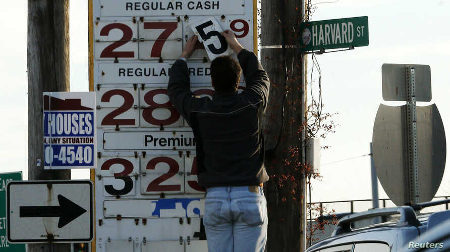 A man changes the price for a gallon of gasoline at a gas station in Medford, Massachusetts, Dec. 4, 2014.