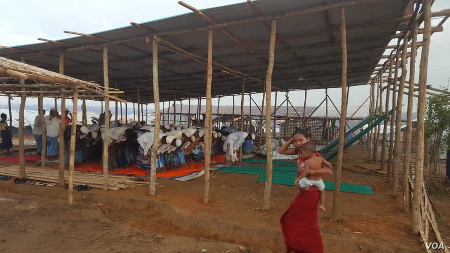 Rohingya men pray under a temporary shelter in the Kutupalong refugee camp in southern Bangladesh, Oct. 2, 2017.