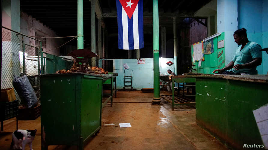 """FILE - A Cuban flag decorates a subsidized state store, or """"bodega,"""" where Cubans can buy basic products with a ration book they receive annually from the government, in downtown Havana, Cuba, Nov. 22, 2017."""