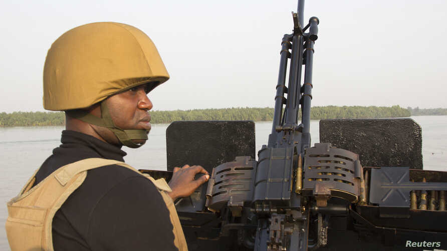(File) A naval officer mans a machine gun on a boat off the Atlantic coast in Nigeria's Bayelsa state Dec. 19, 2013. Pirate attacks off Nigeria have jumped by a third in 2013 as ships passing through West Africa's Gulf of Guinea have come under threa
