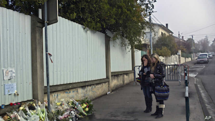 Women pay respects outside the Ozar Hatorah Jewish school, in Toulouse, France, March 23, 2012 where three children and a rabbi were gunned down.