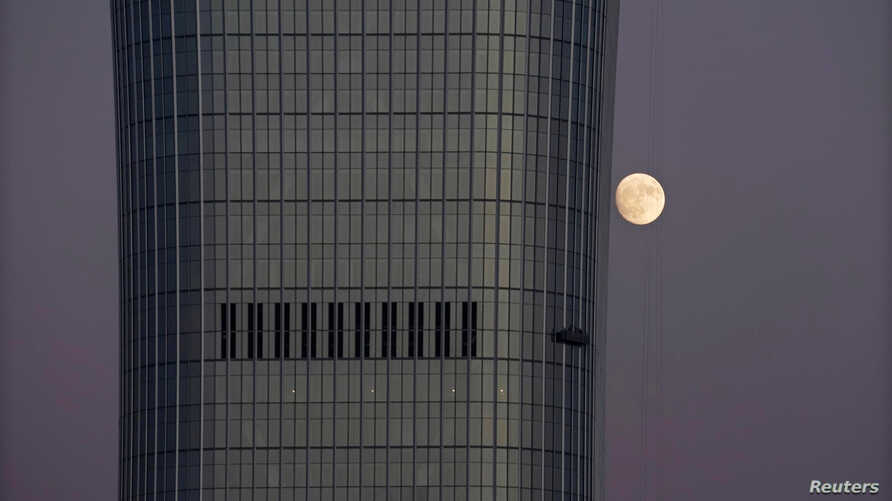 FILE - A moon is seen behind the construction site of China Zun in Beijing's central business area, Nov. 21, 2018.
