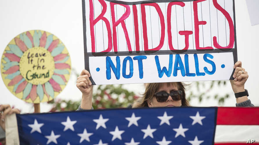 """Lauren Rees holds up a sign during a rally against a scheduled visit by President Donald Trump, March 13, 2018, in San Diego.  Protesters chanted, """"No ban! No wall!"""" near the San Ysidro border crossing, where tens of thousands of people enter the..."""