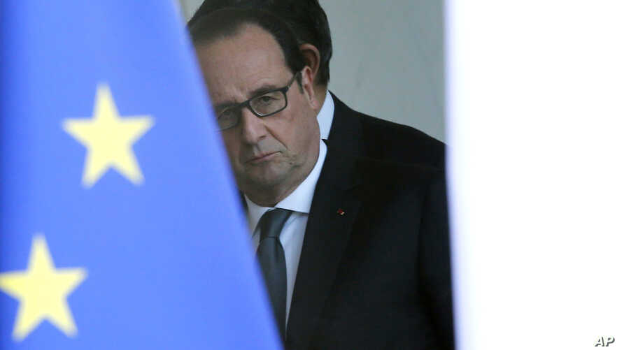 French President Francois Hollande is seen through the glass door after a security meeting at the Elysee palace in Paris, Nov. 14, 2015.