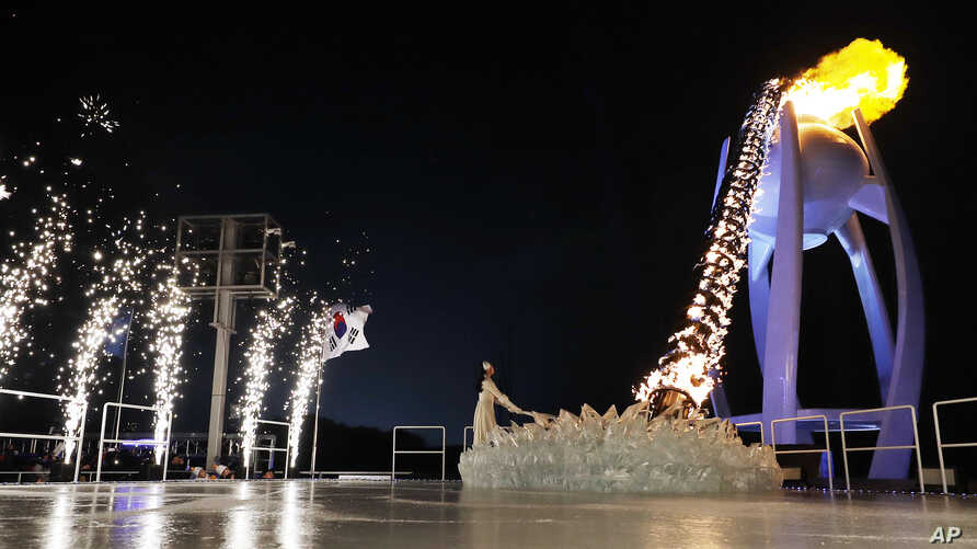 South Korean Olympic figure skating champion Yuna Kim lights the Olympic flame during the opening ceremony of the 2018 Winter Olympics in Pyeongchang, South Korea, Feb. 9, 2018.