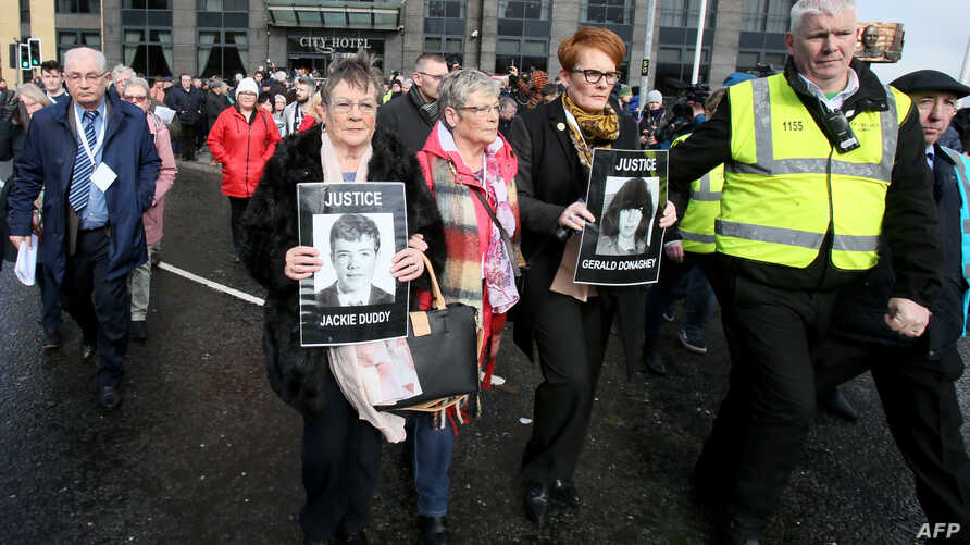Family members of victims of the 'Bloody Sunday' killings walk in procession holding portraits of their killed relatives in Londonderry on March 14, 2019 following the announcement that a former British soldier will be charged with murder over the 19